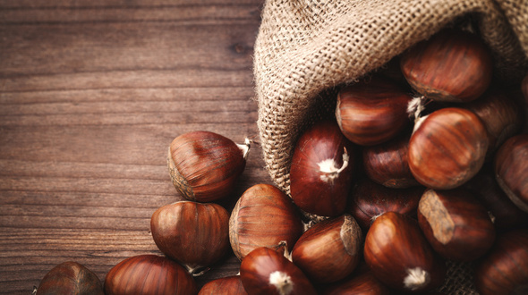 chestnuts, typical autumn winter fruit on background