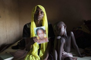 File photo shows Rachel Daniel holding  up a picture of her abducted daughter Rose Daniel as her son Bukar sits beside her at her home in Maiduguri