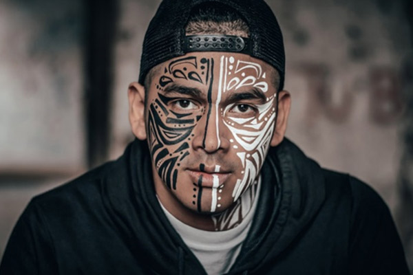 man with black and white face tattoo