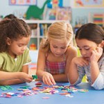 Girls (4-7) playing jigsaw puzzle in classroom