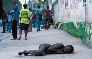 Una dona despullada jeu al mig del carrer, sense ser atesa per ningú, a prop d'un hospital on s'atén malalts de còlera a Port-au-Prince. AFP / HECTOR RETAMAL