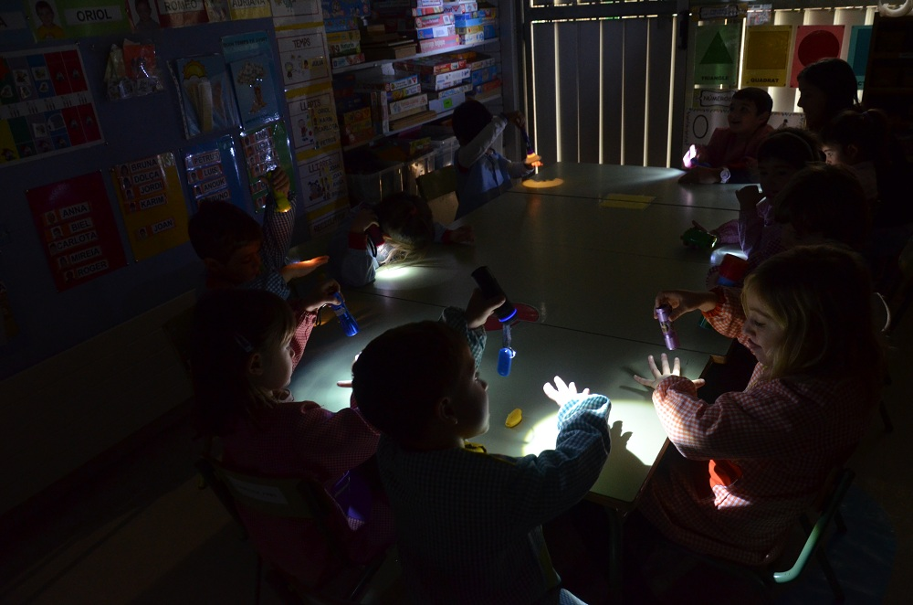 Demanem que cada nen/a porti una llanterna de casa, iapaguem els llums i experimentem què passa.