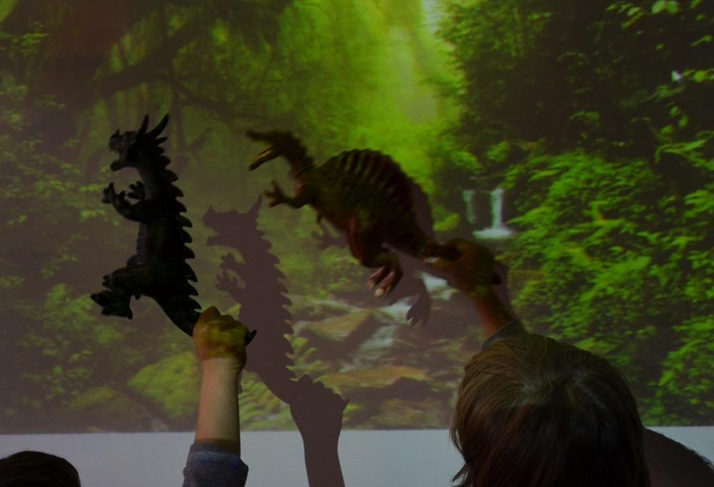 En aquesta sessió els infants van agafar joguines per buscar la seva ombra a la pissarra digital. Tot anava bé fins que es van adonar que la joguina era massa petita i l'ombra gairebé no s'apreciava. Finalment van decidir canviar les joguines per unes altres de més grans i uns dels infants va proposar projectar un paisatge de selva! Tota una experiència!